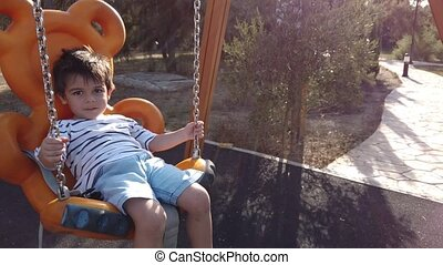 cute 3 years old boy swinging on the swing with his baby brother