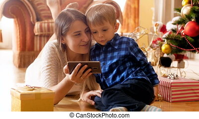 Cute 3 years old toddler boy watching cartoons on mobile...