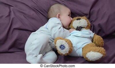 Cute 4 months old baby boy biting teddy bear