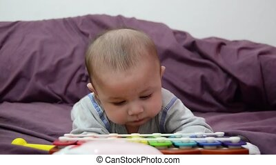 cute 4 months old baby boy looking at colorful xylophone while having tummy time