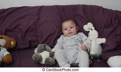 cute 4 months old baby boy on purple bedding with bunny toy