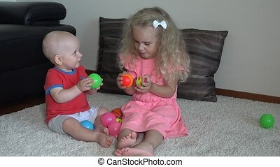 cute 4 years old girl and little brother boy playing with colorful balls at home