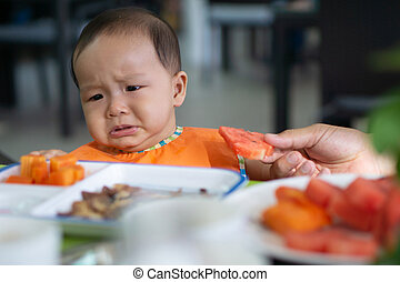 Cute 5-6 month asian baby girl doesn't want to eat watermelon
