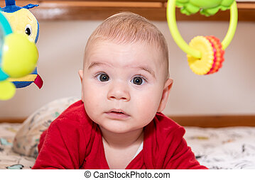 Cute 6 months old little baby boy with curiosity expression on his face surrounded by colourful toys.