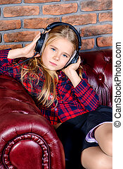 Cute 7 year old girl listening to music on headphones.