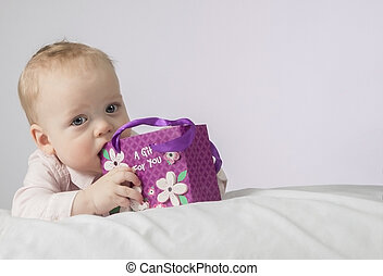 Cute 8 month boy with a gift in a pocket lying on the white blanket and looking at camera. Postcard for mothers day.