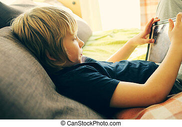 Cute 8 years old boy playing with tablet