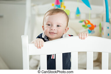 Cute 9 month old baby boy standing crib