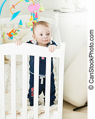 Cute 9 month old baby boy standing in crib