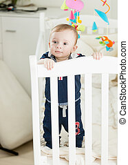 Cute 9 month old boy standing in white wooden crib