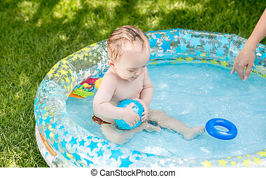 9 months old baby boy playing with ball in pool at garden