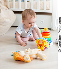 9 months old baby boy playing with colorful toys on floor at...