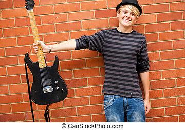 cute, adolescente, músico, segurando, guitarra