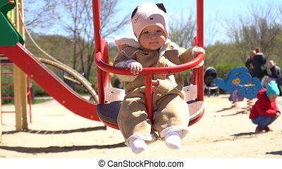 Cute adorable baby girl on swing in slowmo