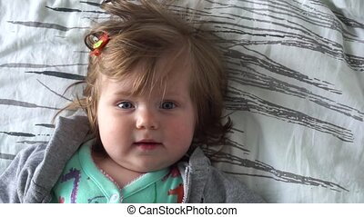 Cute adorable baby girl smiling lying on bed