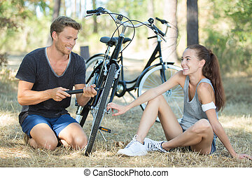 cute adorable couple smiling while fixing bicycle wheel