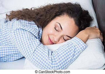 Cute adult girl smiling in her sleep