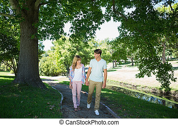 Cute affectionate couple walking hand in hand in the park
