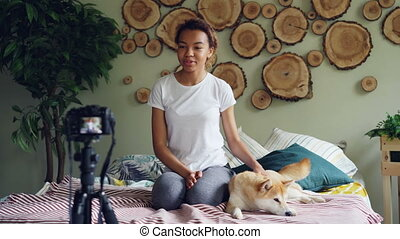 Cute African American teenager blogger is recording...