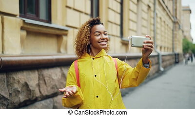 Cute African American teenager is talking to friends online skyping using smartphone and looking at screen standing outdoors in the street and wearing earphones.