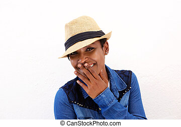 Cute african american woman smiling with hand covering mouth