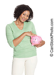 Cute African American woman standing with a pink piggy bank