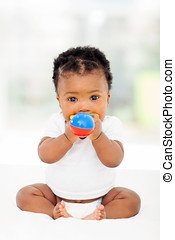 african baby girl biting her toy - cute african baby girl...