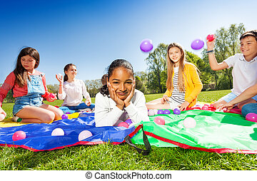 Cute African boy laying on colorful mat in park