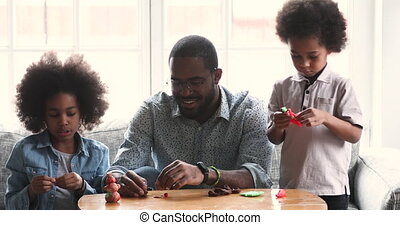 Cute african children and dad sculpting playdough at home