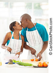 african couple kissing in kitchen