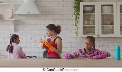 Cute african girl cleaning table with detergent - Lovely ...