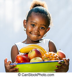 Cute african girl holding fruit bowl. - Close up portrait of...