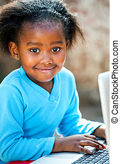 Cute african girl typing on laptop. - Portrait of young ...