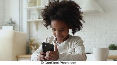 Cute african kid girl holding smartphone enjoying using mobile apps