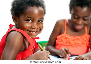 Cute African kid holding crayon with friend in background.