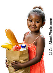 Cute african kid holding groceries in brown bag.