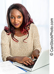 Cute african teen girl typing on laptop.
