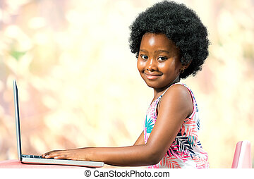 Cute afro american kid typing on laptop.