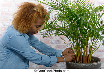 Cute afro woman with green plant