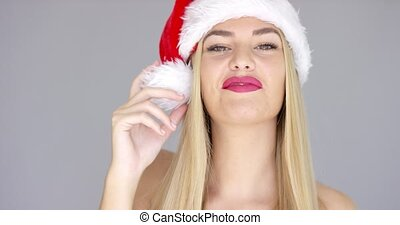 Cute and adorable blond girl playing with Santa Claus Hat