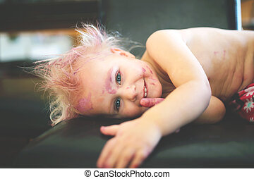 Cute and Naughty Painted Toddler Smiling at Camera