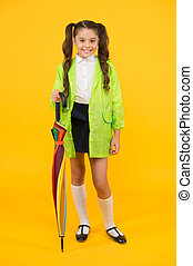 Cute and practical style. Happy small girl holding umbrella cane with elegant style on yellow background. Little child smiling in rainy day style outfit. Fashion style for rainy season