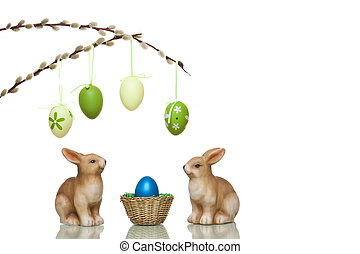Cute and sweet Easter rabbits sitting beside Easter nest with egg. In Background are catkins branches with hanging eggs visible. Isolated on white.