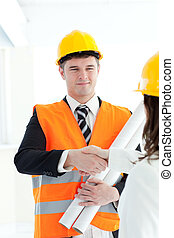 Cute architect discussing with his colleague against a white...