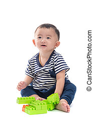 Asian baby is playing with plastic construction toys over white background, isolated
