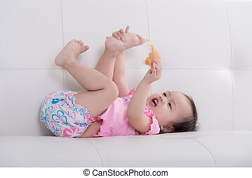 Cute Asian baby lying on sofa and eating bread at home.