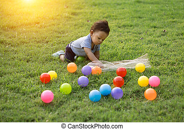 Cute asian baby playing colorful ball in green grass