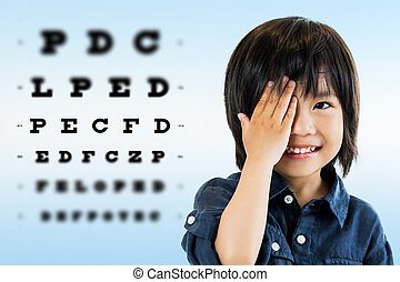 Cute asian boy doing eye test. - Close up portrait of cute...