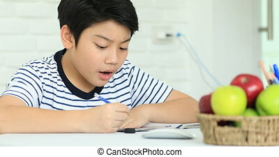 Cute asian boy doing homework at home with smile face.