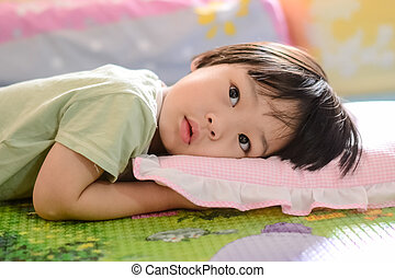 Cute Asian child lying on bed.
